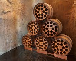 six light brown wooden drums arranged as triangle and holes on the surface as the bottle shelves