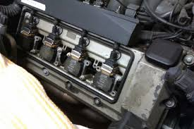 disconnect the ignition coils by lifting the metal bracket and pulling the plugs then remove the all the nuts one coil on each side has a ground