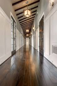 wood ceiling lighting. long hall features a sloped ceiling dark stained wood beams and caged lanterns with paper shades also top part of walls painted gray lighting e