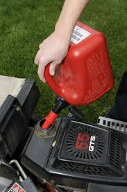 a spill proof gas can is being used to fill a lawn mower