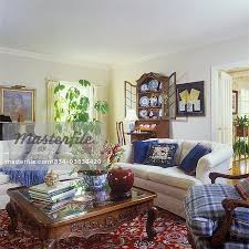 living room creamy walls red oriental rug white couches cabriole leg oak coffee table books snapdragon fl arrangement in bowl blur pillows