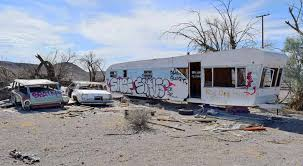 a dilapidated cabin next door to this abandoned trailer reads red dog mine over the front door that explains it huh