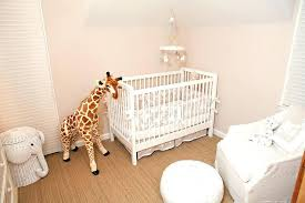 white and beige girl nursery with wicker elephant hamper giraffe rug for