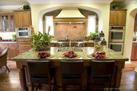 this luxury kitchen has a warm color scheme a large island and beautiful seafoam