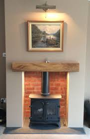 CP Wood Burning Stoves, Yeoman Exe with lighting and brick slip effect.  Brick slip in recesses either side and inside the fireplace opening.