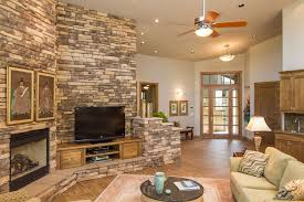 brick cream stone retaining wall designs ideas with under mount wall fireplace also white sectional sofa combine round coffee table over wooden ceiling fan