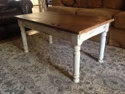 white wooden coffee table plus four cylinder legs also brown wooden counter top placed on the