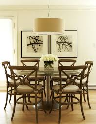 beautiful dining space with linen drum pendant over stainless steel dining table french cafe dining chairs and art