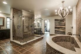 rustic master bathroom with a chandelier stone accent walls and tile flooring
