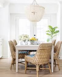 coastal relaxed dining room with rattan dining chairs pole rattan frame and legs in natural seagr tied with lakanai rope and wide plank hardwood
