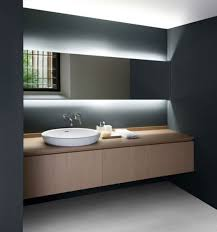 minimal countertop washbasin and gorgeous lighting behind the mirror
