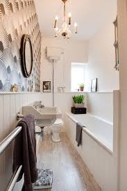 long bthroom with long small bathtub wooden flooring white sin chandelier white