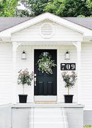 striking black front door on cl white house wreath planters with topiaries and big house numbers thistlewoodfarms