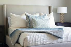 gray wingback bed with gray and blue pillows and gold quatrefoil lamps