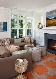 small living room with orange grey rug beige corner sofa wih pillows three brown