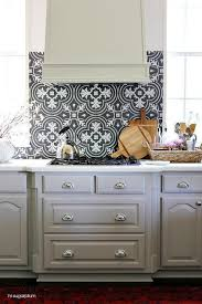 black and white mosaic tile kitchen backsplash with gray kitchen hood