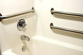 a bath tub that has grab bars installed inside ada handicap bathroom bar height
