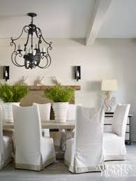 in the dining room texture in the form of limewashed floors a rough hewn mantel and a light elm pedestal dining table and slipcovered chairs
