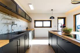 light wood and black make up the color scheme in this modern kitchen it s a