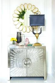 remarkable small entryway wall ideas with flower shaped mirror over foyer console cabinet using metallic paint