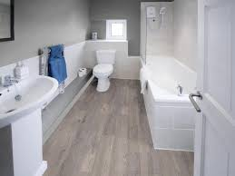 bathroom with wood flooring and a white toilet sink and tub