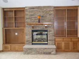 Interior. beige Fireplace Base added by black metal fire box and brown  wooden mantel shelf