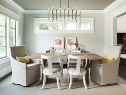 elegant dining room with jonathan adler meurice rectangular chandelier hung from dark gray ceilings over a simple wooden dining table lined with