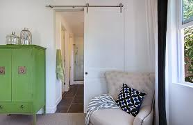 beautiful bedroom features a modern white barn door on rails sliding open to the bathroom flanked by a green chinoiserie cabinet to the left and corner