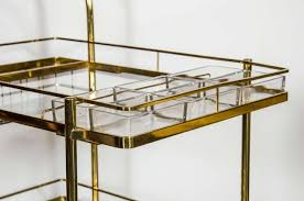 sophisticated midcentury modern bar cart in brass with glass