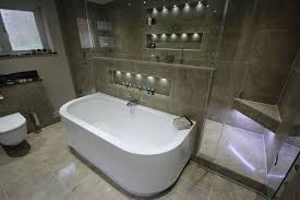 led lit storage recesses provide ample storage for all sorts of lotions and potions in this bathroom ample shower room