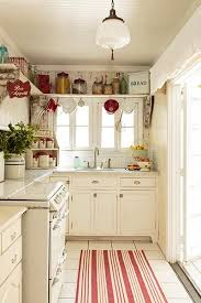 flea market decor stands on an open shelf wrapping around the wall near the ceiling of this vine look kitchen in shades of white with red accents in this