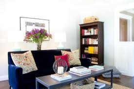 white eclectic living room with blue velvet sofa