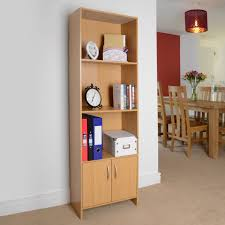 3 shelf bookcase with cupboard and items angled view in living room