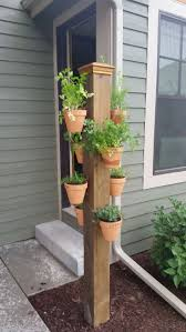 Vertical herb garden in clay pots on a pole using hangapot, the hidden  flower pot