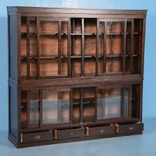 this beautiful antique japanese bookcase has 8 sliding glass doors with shelves inside and four drawers