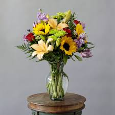 a stunning arrangement of sunflowers lilies roses and assorted seasonal flowers are