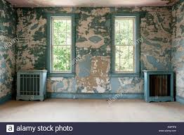 Pair of distressed blue radiator covers in room with extremely cracked and  peeling wall paint