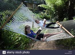 Girl and boy reading on a huge hammock at Punga Cove, Queen Charlotte  track, Marlborough, New Zealand