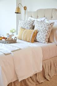 all the beds in my home are topped with a tray basket or bed tray with legs for the master bedroom i chose a gray tone oval basket to hold a couple books