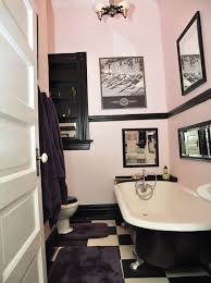 View in gallery Light pink and black bathrom with retro wall art