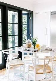white wishbone chairs airy white and black dining area the breakfast table sits on one end of the kitchen where french doors open out to an english