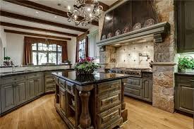 luxury traditional kitchen with raised panel dark cabinets with antique black granite counter stone oven surround