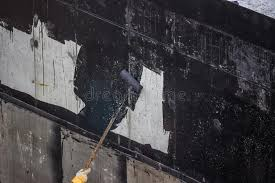 waterproofing worker painting exterior concrete wall with tar i stock photo image of