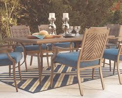 outdoor dining table with beige chairs with blue cushions on top of a blue and green