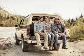 Three people sitting on back of pickup truck, arms around shoulders ...