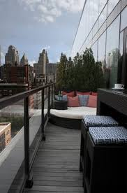 exquisite modern apartment balcony design with modern glass balcony railings design also old style floorboards also plait day bed with red and blue cushions balcony condo patio furniture