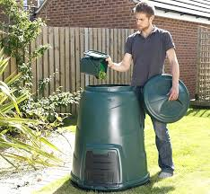 composting kitchen bins a man adding the contents of his kitchen into a garden compost bin composting kitchen bins