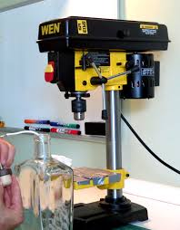 drill press labeled. after laying the sticks out about a 1/4\u2033 apart i simply duct taped them down. tape acted like buffer for glass bottles from metal table. drill press labeled m