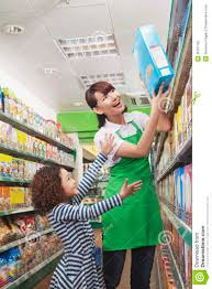 female s clerk helping a little girl reach a cereal box stock female s clerk helping a little girl reach a cereal box