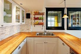 country kitchen with maple wood countertops and white cabinets